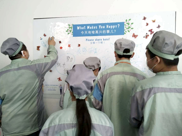 """Employees gathered around a whiteboard, writing the answer to a question: """"What makes you happy?"""""""